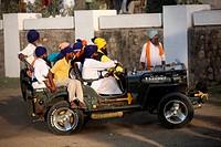 Group of Nihangs or Sikh warriors driving jeep during Hola Mahalla celebration at Anandpur sahib in Rupnagar district , Punjab , India