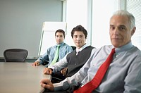 Portrait of three businessmen posing for the camera in a conference room