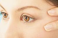 Young Woman Examining Skin Around Eyes