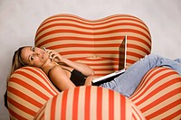 Woman Lying in Armchair Using Cell Phone and Laptop