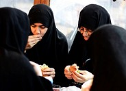 Muslim girls eating fish sandwiches by the Galata bridge in Istanbul