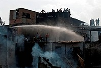 Firefighters dousing fire using snorkel in Behrampada slums ; Bandra ; Bombay Mumbai ; Maharashtra ; India 18-June-2009