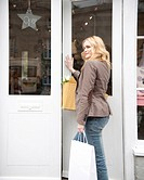 A woman entering a shop, smiling