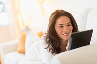 Woman on sofa using tablet pc