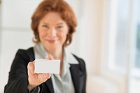 Portrait of businesswoman holding blank business card