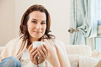 Woman having cup of coffee on sofa