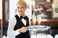 Portrait of waitress holding champagne flutes on tray