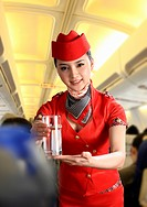 Flight attendant serving people on airplane,portrait