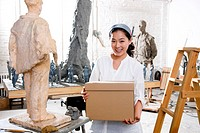 A female carrying a box in studio