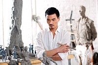 A male sculpturer sculpturing in studio