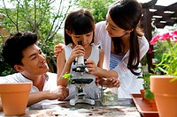 A girl using microscope with parents outdoors