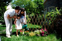 Oriental family watering flowers outdoors