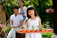 A girl holding some flowerpots with parents outdoors