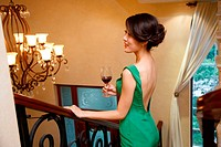 Young woman holding glass of red wine on stairs
