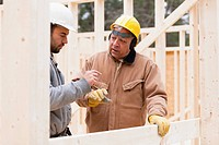 Construction foreman reviewing home under construction