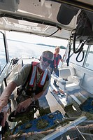 Two engineers on service boat preparing to take water samples from public water supply