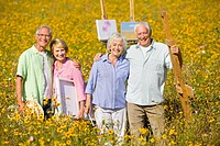 Portrait of smiling couples with paintings and easels among wildflowers in sunny meadow