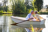 Smiling couple kissing in rowboat on lake