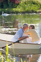 Senior couple kissing on rowboat on sunny lake
