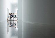 Portrait of business people sitting in circle in corridor