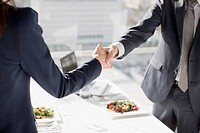 Businessman and businesswoman shaking hands at table with lunch