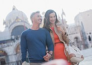 Smiling couple holding hands and walking through St. Mark's Square in Venice