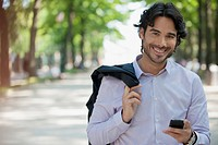 Portrait of smiling man holding cell phone in park
