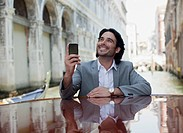 Smiling businessman holding cell phone and leaning on boat in canal in Venice