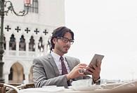 Businessman using digital tablet at sidewalk cafe in Venice