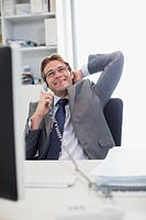 Smiling businessman talking on telephone at desk in office