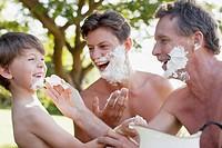 Playful multi_generation men applying shaving cream to faces