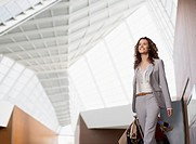 Smiling businesswoman carrying suitcase in airport