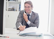 Smiling businessman talking on telephone and writing