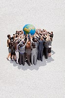 Crowd of business people in huddle lifting globe overhead