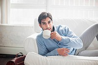 Man drinking cup of coffee on sofa