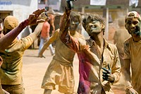 Boys celebrating holi festival enjoying dancing and playing color , Katni , Madhya Pradesh , India NO MR