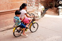 Little girl and boy on small bicycle , Jodhpur , Rajasthan , India MR704