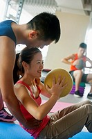 Chinese woman working with personal trainer in gym