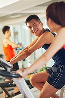 Chinese couple riding stationary bicycles in gym