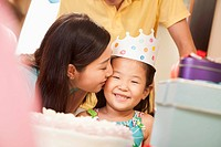 Chinese mother kissing daughter at party