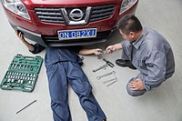 Chinese mechanics working in garage