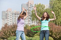 Chinese mother and daughter hula hooping in park