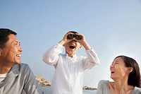 Chinese boy using binoculars on beach