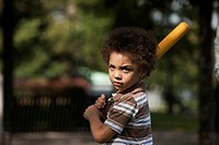 Mixed race boy swinging baseball bat in park