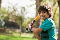 Hispanic boy swinging baseball bat in park