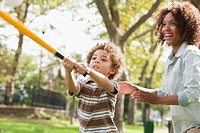 Mother and son playing baseball in park