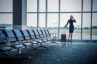 Caucasian businesswoman talking on cell phone in airport