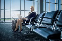 Caucasian businesswoman using laptop in airport