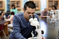 Chinese student at microscope in lab classroom