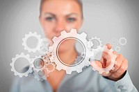 Businesswoman pressing wheels and cogs graphic